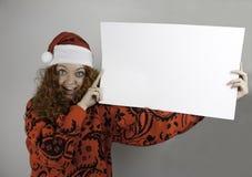 Nätt bärande jultomten hatt för ung kvinna och tomt tecken för innehav Royaltyfria Bilder