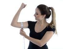 Nätt babe som mäter hennes biceps Royaltyfria Bilder