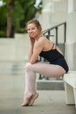 Nätt balettflicka som poseras på den vita bänken Arkivfoto