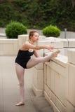 Nätt balettflicka som sträcker henne knäsena Royaltyfria Bilder