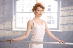 Nätt ballerinaflicka som plattforer, genom stångatt öva Royaltyfri Foto
