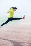 Nätt banhoppning för ung kvinna som bär den gröna sportswearen. Fotografering för Bildbyråer