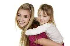 Nätt barnflicka som lite ger flicka en ridtur på axlarnaritt Arkivfoton