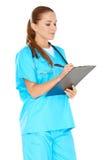 Nätt barnsjuksköterska som skriver upp anmärkningar Royaltyfria Bilder