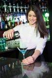 Nätt bartender som häller en blå martini drink i exponeringsglaset royaltyfria foton