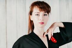 Nätt blåögd kvinna i svart klänning, med röd kastanjetter, ljus Royaltyfria Bilder