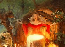 Nätt blond dam ovanför en stor magisk kittel med rök, skognymf i lång ljus röd klänning med lösa muffkockar arkivfoto