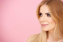 Nätt blond flicka över rosa färg med copyspace Arkivbild