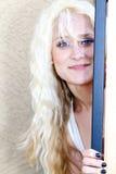 Nätt blond flicka bak en dörr Arkivfoton