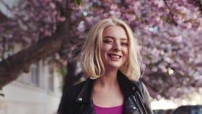 Nätt blond flicka i läderomslag som charmingly tycker om den körsbärsröda blomningen i staden, vänd till kameran och leenden stock video