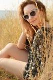 Nätt blond flicka som kopplar av på fält med torrt gräs Royaltyfri Foto