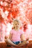 Nätt blond flicka som mediterar på parkera Arkivbilder