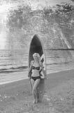 Nätt blond flickamodell som Marilyn Monroe med surfingbrädan på en strand Arkivbilder