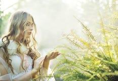 Nätt blond kvinna med ormbunken royaltyfria bilder