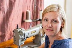 Nätt blond kvinna på symaskinen Arkivfoton