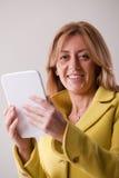 Nätt blond kvinna som använder en minnestavla Arkivfoton