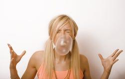 Nätt blond kvinna som blåser gummibubblor arkivbild