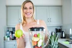 Nätt blond kvinna som förbereder en smoothie royaltyfri bild