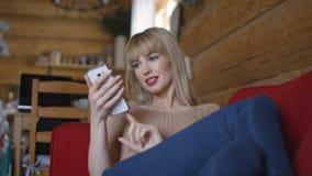 Nätt blond kvinna som hemma smsar på telefonen Royaltyfria Foton