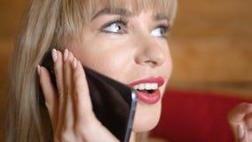 Nätt blond kvinna som hemma talar på telefonen Fotografering för Bildbyråer