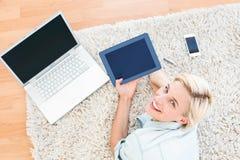 Nätt blond kvinna som ligger på golvet och använder hennes minnestavla Arkivbild