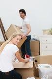 Nätt blond kvinna som packar upp huset Fotografering för Bildbyråer