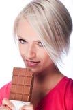 Nätt blond kvinna som rymmer en biten chokladstång arkivbild