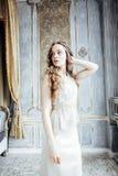 Nätt blond lockig frisyrflicka i ensamt för lyxigt hus inre rikt ungdomarbegrepp royaltyfri foto