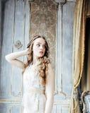 Nätt blond lockig frisyrflicka i ensamt för lyxigt hus inre rikt ungdomarbegrepp fotografering för bildbyråer