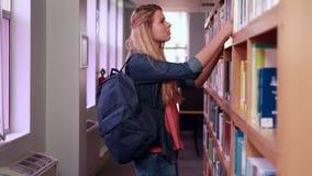Nätt blond student som tar boken från hylla arkivfilmer