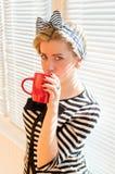 Nätt blond ung kvinna som dricker kaffe eller te Royaltyfri Foto