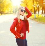 Nätt blont bära för kvinna solglasögon och rött omslag med halsduken i solig höst royaltyfri fotografi