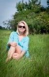 Nätt blont koppla av för flicka som är utomhus- i grönt gräs Fotografering för Bildbyråer