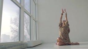 Nätt blont yogakvinnasammanträde, i position och att koppla av för yoga arkivfilmer