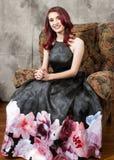 Nätt brunögd rödhårig manflicka som vilar i stol royaltyfri fotografi