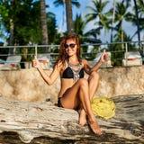 Nätt brunbränd lycklig flicka i baddräkten och solglasögon som visar thum Arkivbilder
