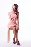 Nätt brunett i ett rosa klänningsammanträde på en stol på vita lodisar Arkivbild