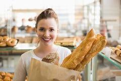 Nätt brunett med påsen av bröd Arkivbild