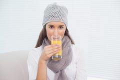 Nätt brunett med vinterhatten på att dricka orange fruktsaft Arkivfoto