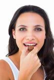 Nätt brunett som äter chokladgodisen Arkivfoton