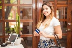 Nätt brunett som betalar med en kreditkort royaltyfria foton