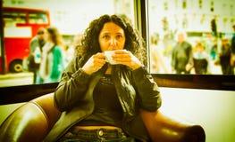 Nätt brunett som dricker kaffete royaltyfria bilder