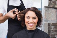 Nätt brunett som får henne hårsnittet arkivbild