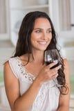 Nätt brunett som har ett exponeringsglas av vin Arkivbild
