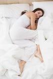 Nätt brunett som ligger i säng som ler på kameran Royaltyfri Fotografi