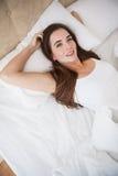 Nätt brunett som ligger i säng som ler på kameran Fotografering för Bildbyråer