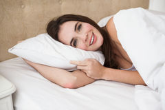 Nätt brunett som ligger i säng som ler på kameran Royaltyfri Bild