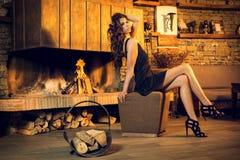 Nätt brunett som poserar nära den brinnande spisen Arkivfoton