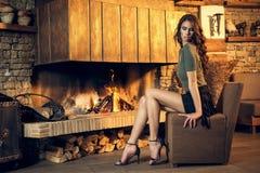 Nätt brunett som poserar nära den brinnande spisen Royaltyfri Foto