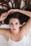 Nätt brunett som poserar på säng Arkivfoto